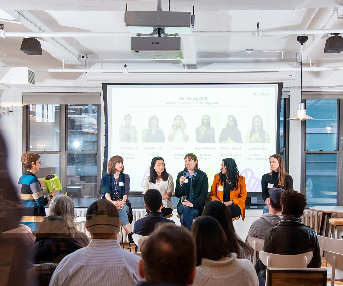 women speaking on a panel in office